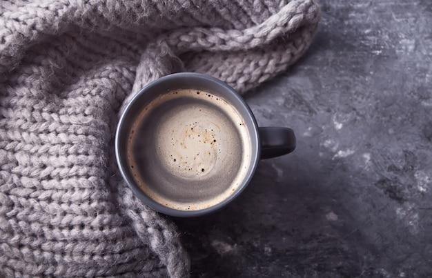 Szary kubek kawy i szalik na szarym stole. koncepcja jesień. minimalizm.