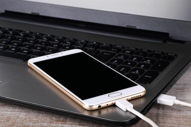 Szary laptop i biały telefon (smartfon) połączone kablem do transmisji danych na drewnianym stole. transfer danych. wymiana informacji