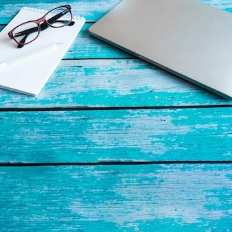 Szary laptop na niebieskim drewnianym stole