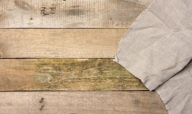 Szary lniany ręcznik kuchenny na stole ze starych drewnianych desek, widok z góry, kopia przestrzeń