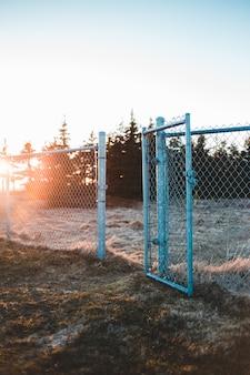 Szary metalu ogrodzenie na brown trawy polu podczas zmierzchu