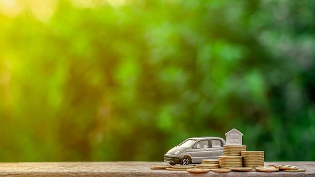 Szary miniaturowy model samochodu i mały dom na stosie monet.