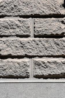 Szary mur z cegły cementowej na zewnątrz tło