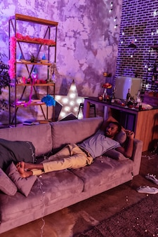 Szary, niechlujny trener. kac afroamerykanin odpoczywa na brudnej, poplamionej kanapie po głośnej alkoholowej imprezie