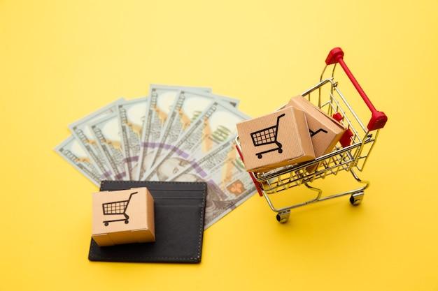 Szary portfel z banknotami stu dolarowymi, pudełkami dostawy i wózkiem na zakupy na żółtym tle