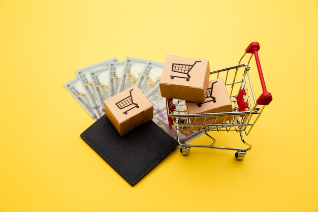 Szary portfel z banknotami stu dolarowymi, trzema pudełkami dostawy i wózkiem na zakupy na żółtym tle.