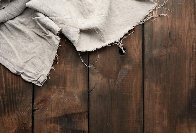 Szary ręcznik kuchenny na brązowym tle drewnianych, widok z góry, miejsce