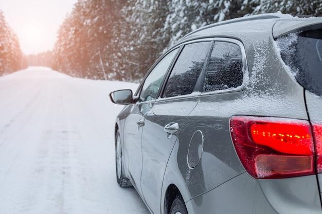 Szary samochód na zimowej drodze w śnieżnej pogodzie. widok z boku — obraz