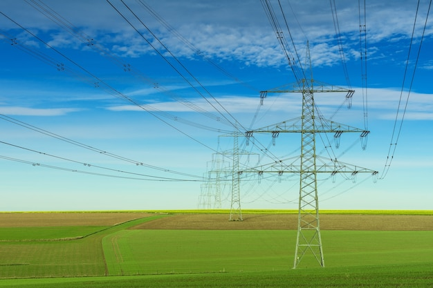 Szary słupek elektryczny pod biało-niebieskim pochmurnym niebem