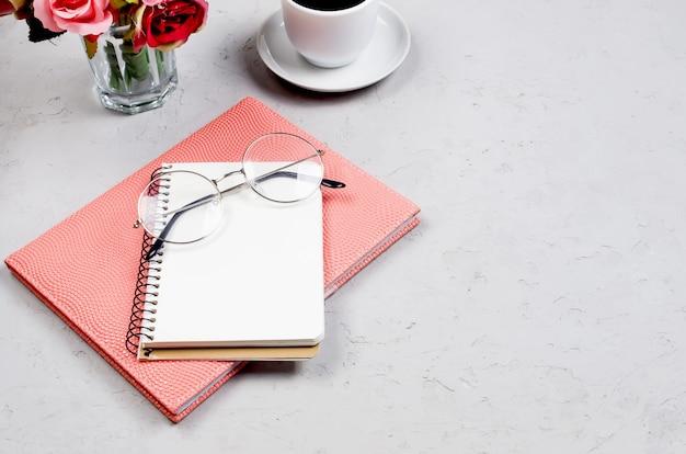 Szary stół biurko z notebookami, puste puste, materiały eksploatacyjne, okulary i filiżankę kawy. widok z góry z miejscem na tekst. leżał płasko. minimalne biuro w domu lub nowoczesna przestrzeń robocza dla freelancerów.