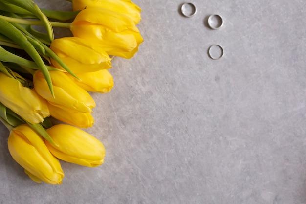 Szary stół z żółtymi kwiatami, tulipany i pierścienie
