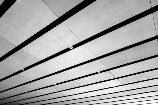 Szary sufit z listwami i lampami