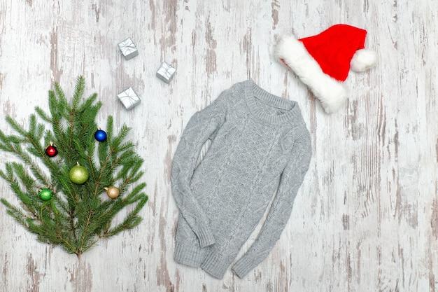 Szary sweter, czapka mikołaja i gałąź jodła na drewnianym tle. koncepcja mody