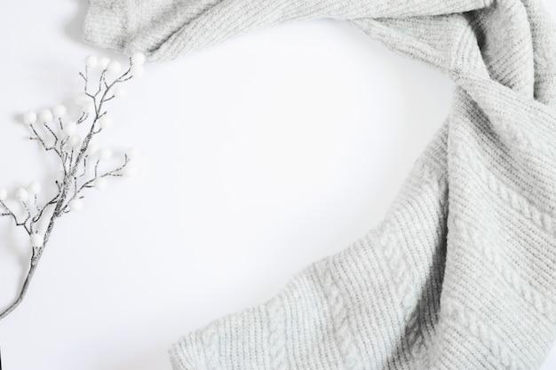 Szary sweter i biała gałąź na białym tle