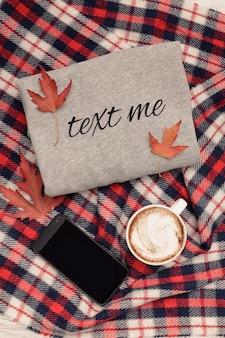 Szary sweter, kratka, kubek kawy i smartfon. jesienne liście. modna koncepcja
