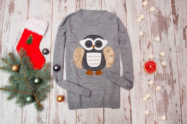 Szary sweterek z sową na drewnianym tle. gałąź choinkowa z ozdobami świątecznymi, pończochą, girlandą, prezentem