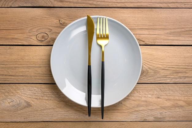 Szary talerz z widelcem i nożem na drewnianym stole