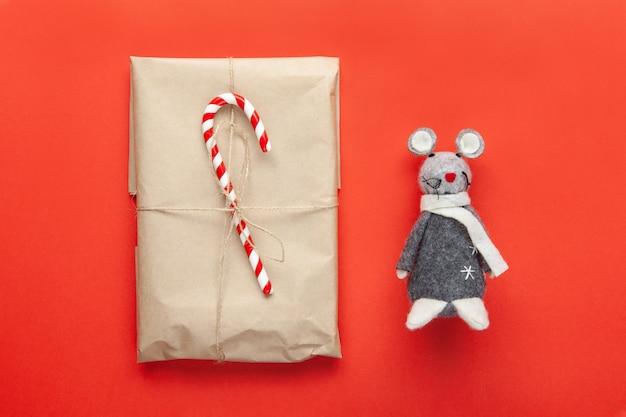 Szary zabawkowy szczur, symbol 2020 roku na chińskim kalendarzu i świąteczny prezent zawinięty w papier rzemieślniczy