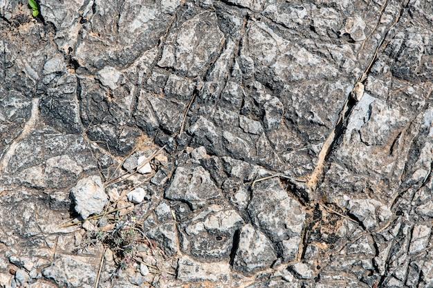 Szary żwir z kamienia ze śladami suchych gałązek i drobnymi kamykami, które sprawiają, że idealnie nadaje się do tekstury