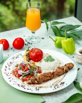 Szaszłyk jagnięcy podawany z ryżem, pomidorem, ogórkiem i sałatką z cebuli, grillowanymi warzywami