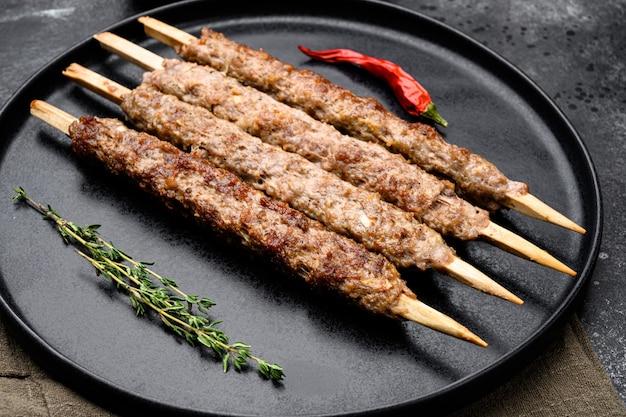 Szaszłyk na patyku, z zestawu mielonego mięsa baraniego, na talerzu, na czarnym ciemnym tle kamiennego stołu