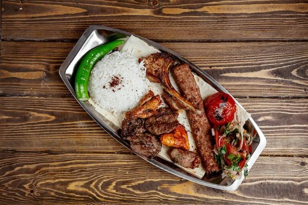 Szaszłyk z mięsa i kurczaka z ryżem i posiekaną cebulą
