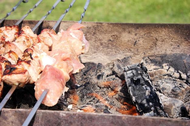 Szaszłyki mięsne na szaszłykach grillowane są na świeżym powietrzu. koncepcja pikniku.