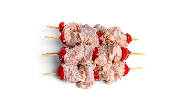 Szaszłyki z kurczaka surowego z pomidorami cherry na białym tle. souvlaki na białym tle.