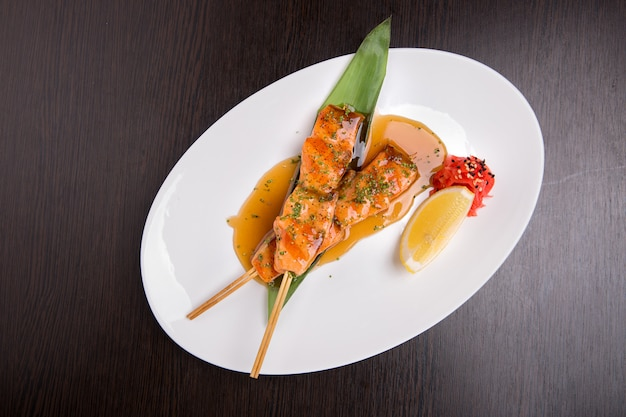 Szaszłyki z łososia, z sosem i cytryną, na białym talerzu, na desce