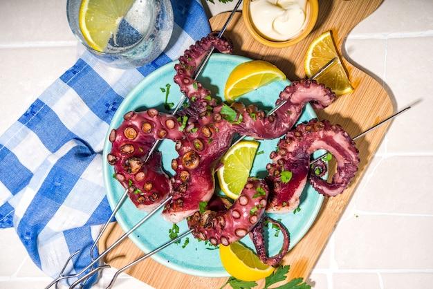 Szaszłyki z owoców morza, ośmiornica na szaszłykach z cytryną, sosem i ziołami. dieta zdrowa koncepcja pikniku, na kafelkowym letnim słonecznym tle widok z góry miejsca kopiowania