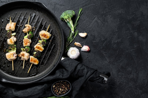 Szaszłyki z piersi kurczaka z grilla. brokuły. czarne tło. widok z góry. miejsce na tekst
