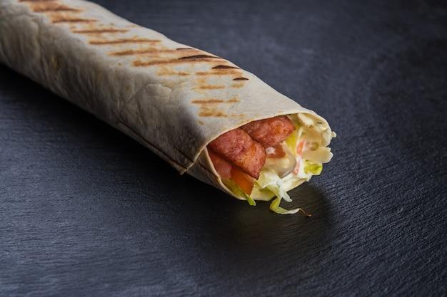 Szawarma kebab z kiełbasą na czarnym teksturowanym kamieniu