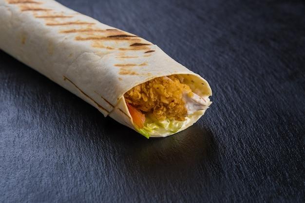 Szawarma kebab z kurczakiem na czarnym teksturowanym kamieniu