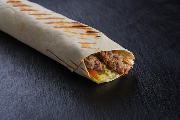 Szawarma kebab z wołowiną na czarnym teksturowanym kamieniu