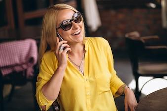 Szczęśliwa blondynki włosy kobieta opowiada na telefonie