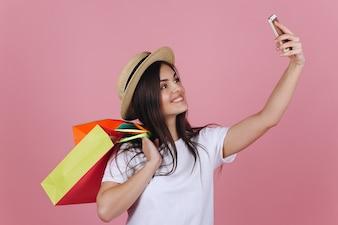 Szczęśliwa dziewczyna z kolorowymi torba na zakupy bierze selfie na jej telefonie