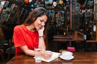 Szczęśliwa kobieta pisze shcedule w pamiętniku z filiżanką kawy na biurku w caf�