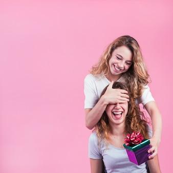 Szczęśliwa kobieta zakrywa jej żeńskich oczy trzyma prezenta pudełko przeciw różowemu tłu