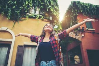 Szczęśliwa młoda kobieta cieszy się podróż podnosi jej ręki w miastowym. Koncepcja życia kobiety.