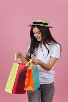 Szczęśliwa młoda kobieta używa jej telefon pozuje z kolorowymi torba na zakupy w studiu