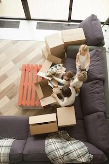 Szczęśliwa rodzina i dzieciaki odpakowywa pudełka poruszający wewnątrz, odgórny widok