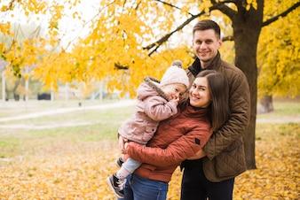 Szczęśliwa rodzinna pozycja i ono uśmiecha się w jesieni uprawiamy ogródek