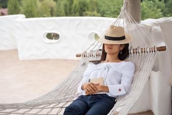 Szczęśliwa zrelaksowana kobieta śpi na hamaku