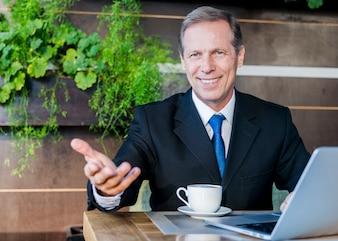 Szczęśliwy biznesmen robi ręka gestowi z filiżanką kawy i laptopem na biurku