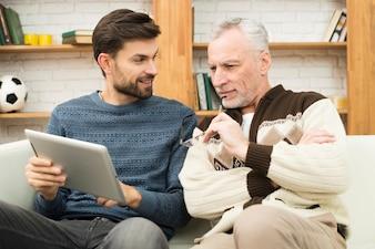 Szczęśliwy młody facet i starzejący się mężczyzna używa pastylkę na kozetce