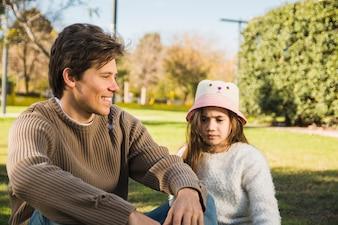 Szczęśliwy ojca obsiadanie przed jego córką w parku