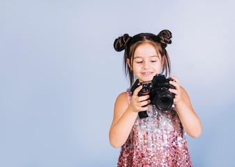 Szczęśliwy portret dziewczyna patrzeje kamerę przeciw błękitnemu tłu
