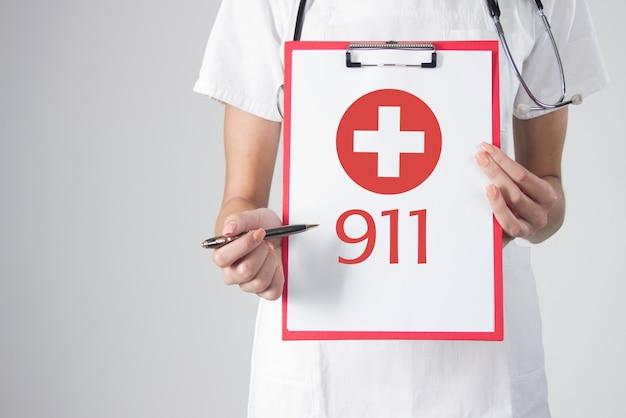 Szczegã³å,y lekarza ze stetoskopem gospodarstwa schowka z medycznego ikonę krzyå¼yka. znak alarmowy. zadzwoń na karetkę pogotowia 911. ilustracja awaryjnego medycznego. na białym tle.