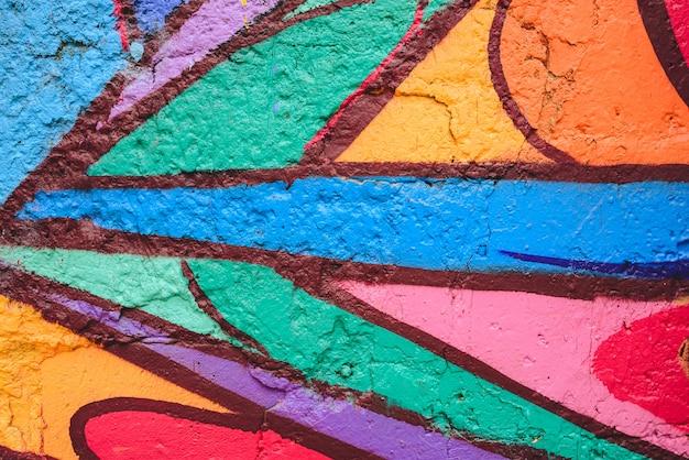 Szczegół anonimowi uliczni graffiti z wiele kolorami, rozochocony miastowy tło.