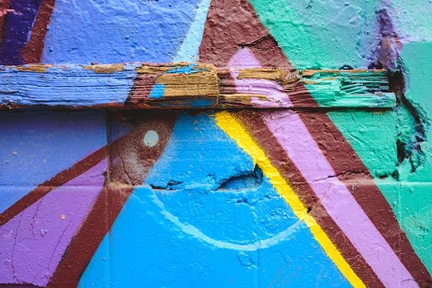 Szczegół anonimowy uliczny graffiti z wiele kolorami, rozochocony miastowy tło.